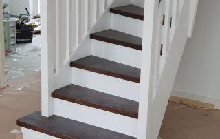 Lantlig U-trappa med betsade ektrapp steg och vita vanger och räckesståndare