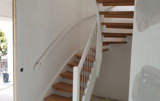 Öppen U-trappa. Steg i lackad ek och sidovang i vitmålat utförande. Räcke i rostfritt stål.